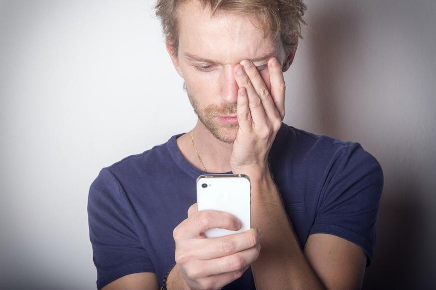 Un homme se tenant la tête devant son téléphone.